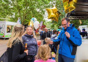 HWG Mitarbeiter verteilt Luftballons an Kinder auf dem Laternenfest