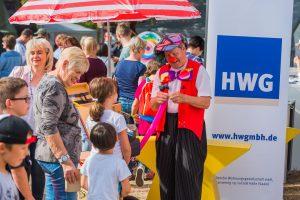 Unterhalter steht am HWG-Stand am Parkfest und erfreut Kinder