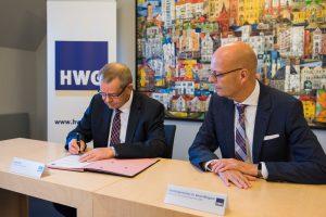 Der HWG-Geschäftsführer und der HWG-Aufsichtsratsvorsitzende unterschreiben die freiwillige Selbstverpflichtung