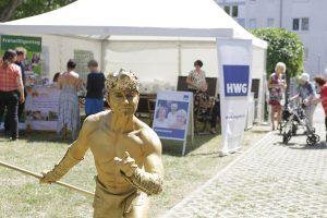 Unterhalter als Griechischer Gott posiert vor dem HWG-Infostand