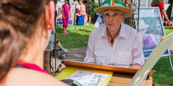Eine Dame mit Strohhut lässt sich zeichnen