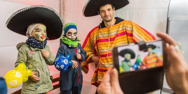 Zwei Kinder sowie ein verkleideter Mexikaner schießen ein Foto