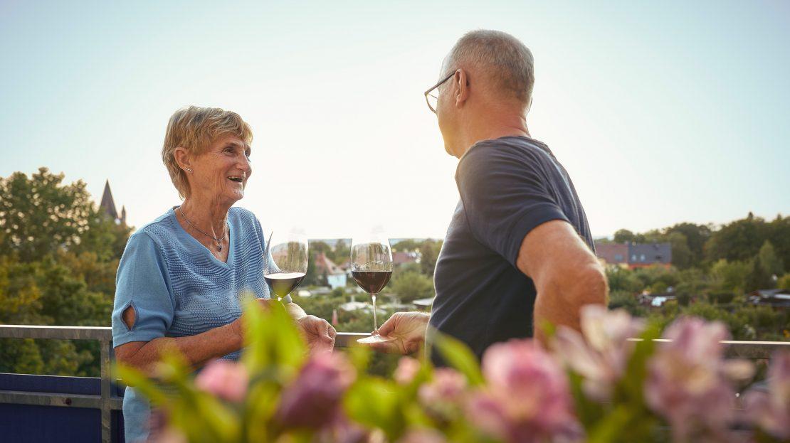 Ein älteres Paar steht mit einem Glas Wein auf dem Balkon und unterhält sich