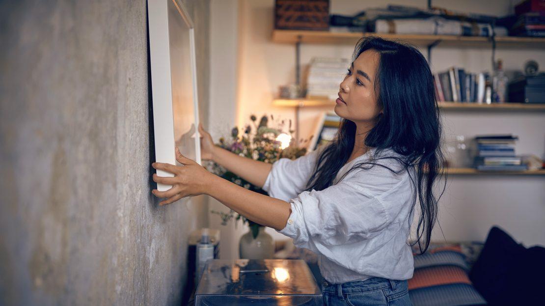Eine junge Frau hängt ein Bild an die Wand