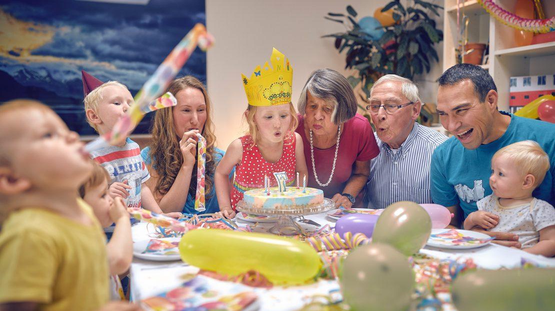 Eine Familie sitzt lachend am dekorierten Geburtstagstisch, ein junges Mädchen pustet die Kerzen auf ihrem Geburtstagskuchen aus
