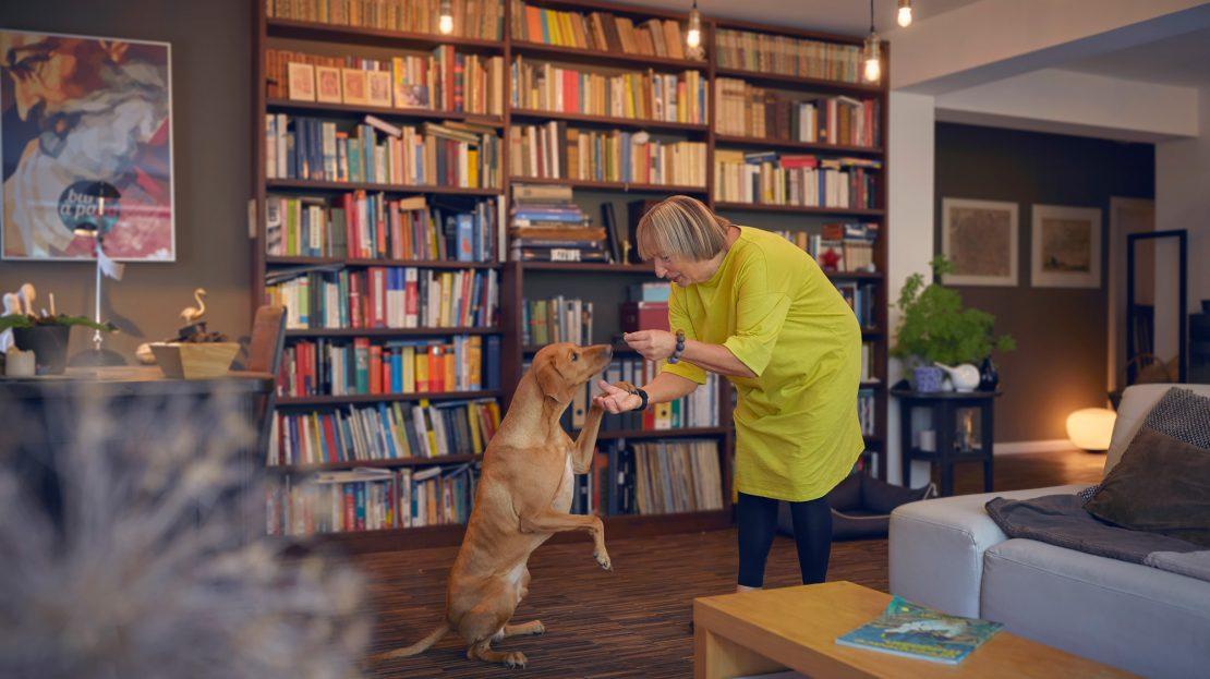 Eine ältere Dame füttert ihren Hund mit einem Leckerli