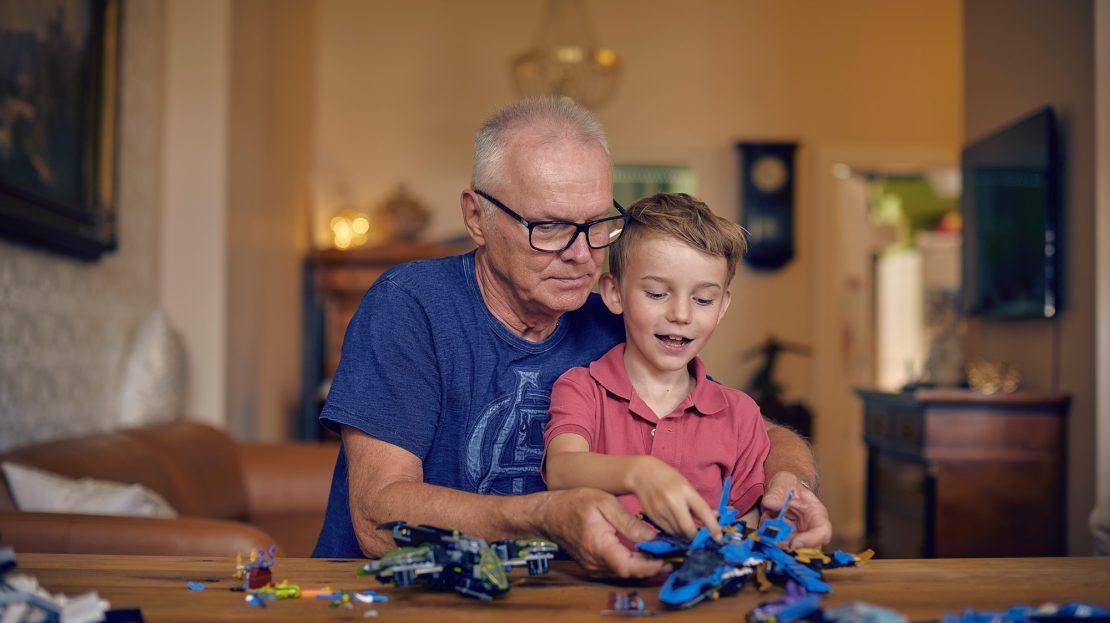 Ein älterer Herr spielt mit seinem Enkel am Tisch