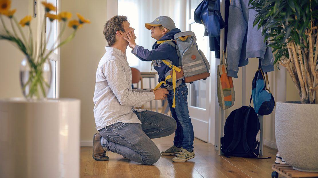 Ein Vater kniet zu seinem Sohn und verabschiedet sich von dem mit seinem Schulranzen bepackten Jungen