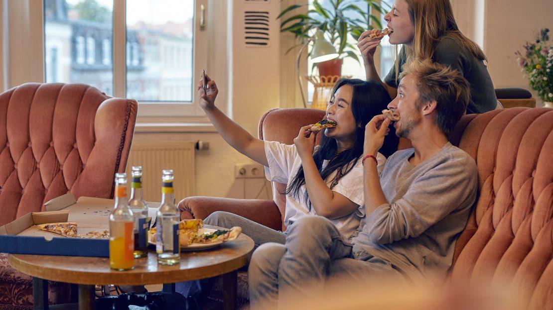 Drei junge Erwachsene auf dem Sofa, essen Pizza und schießen ein Selfie