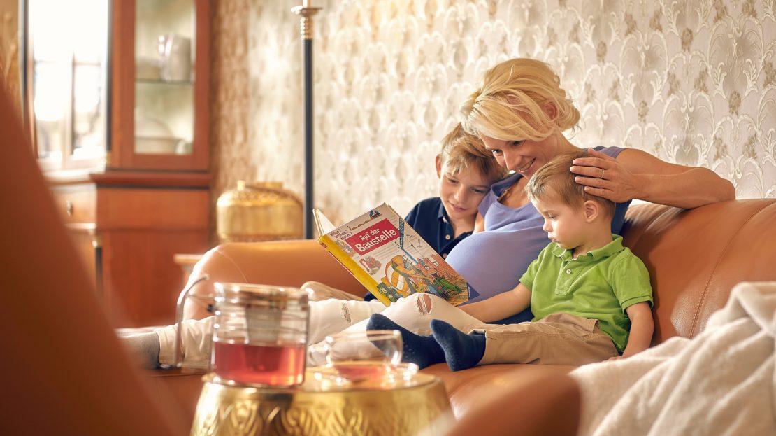 Eine Schwangere sitzt mit ihren beiden Söhnen auf dem Sofa und liest mit ihnen in einem Kinderbuch