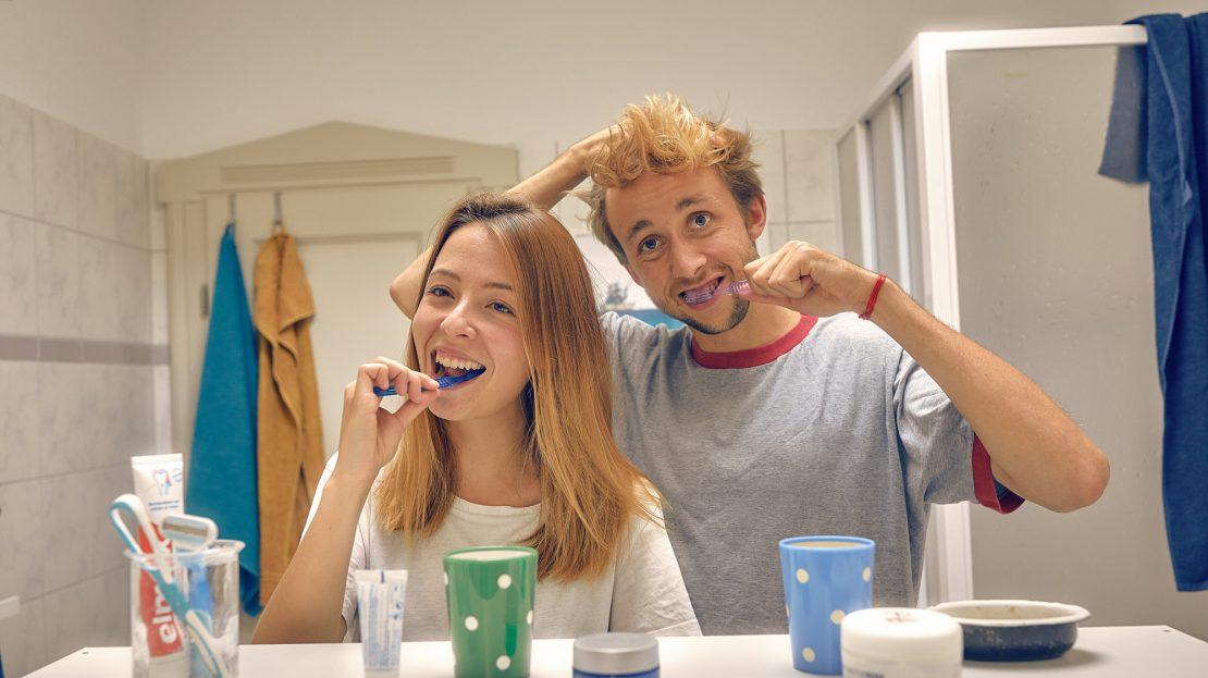 Ein Pärchen steht vorm Badezimmerspiegel und putzt gemeinsam Zähne