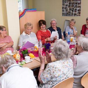 Senioren sitzen freudig gemeinsam am Tisch