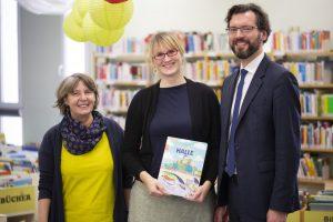 Frau Heinicke, Frau Faust und Herr Schirr halten das neue Wimmelbuch in der Hand