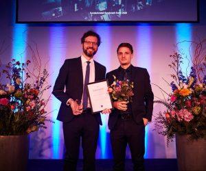 zwei adrette junge Männer, lächelnd auf der Bühne mit Preis und Blumen in der Hand
