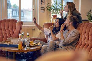 Drei Junge Menschen sitzen gemeinsam auf dem Sofa und machen ein Selfie, während sie Pizza essen.