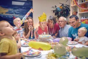 Kind mit Geburtstagskrone am Tisch, um den Tisch sitzt eine lachende Familie bestehend aus Großeltern, Vater, Mutter und weiteren Kindern. Alle pusten an der Geburtstagskerze auf der Torte, die vor dem Mädchen steht.