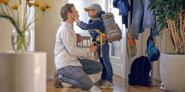 Vater und Sohn im Flur vor der Haustür. Der Vater kniet zum Sohn und verabschiedet sich vom mit dem Schulranzen aufgepackten Jungen.
