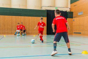 Zwei Kinder in rotem Trikot laufen aufeinander zu, einer von ihnen dribbelt einen Fußball